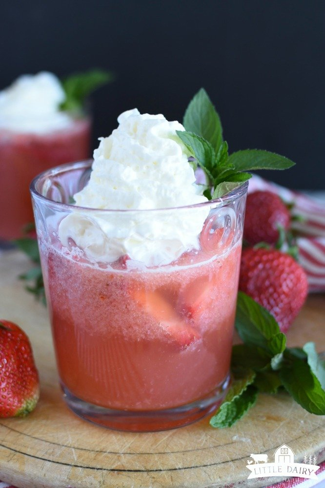 A fizzy strawberry drink in a glass with whipped cream on top of it.