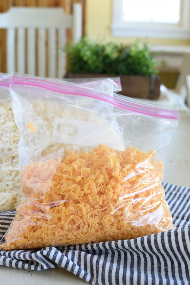 Grated cheddar cheese in a gallon sealable bag on a black and white striped napkin