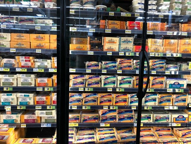 Cheese case at the grocery store with lots of varieties of cheese