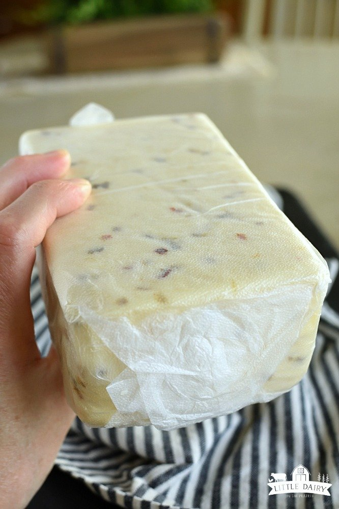 Brick of Pepper Jack cheese wrapped in press and seal wrap, held in a hand