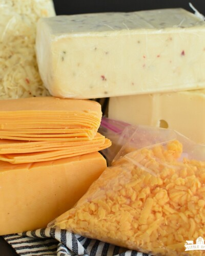 Stacks of cheese, pepperjack, swiss, cheddar, grated cheese in a bag, and sliced cheese