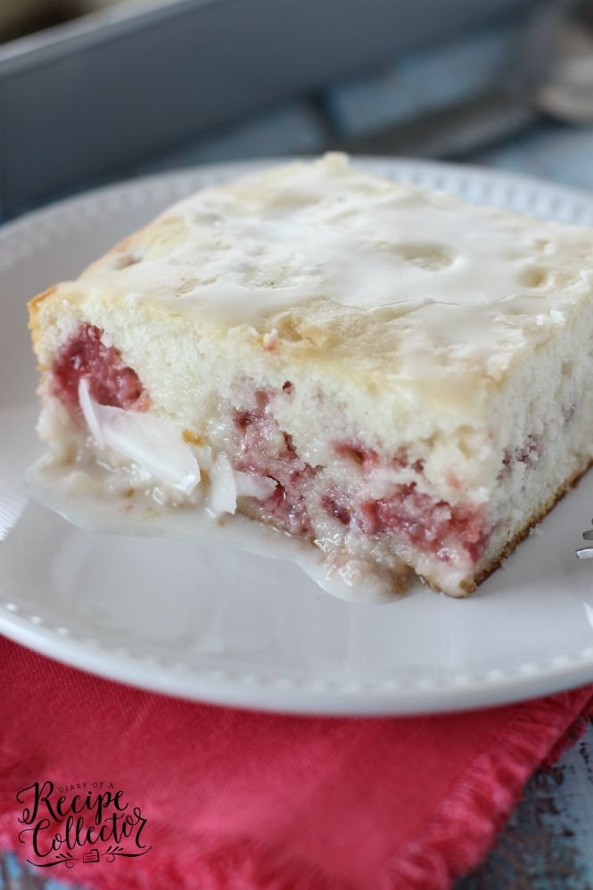 white strawberry cake with sour cream glaze on top on a white plate