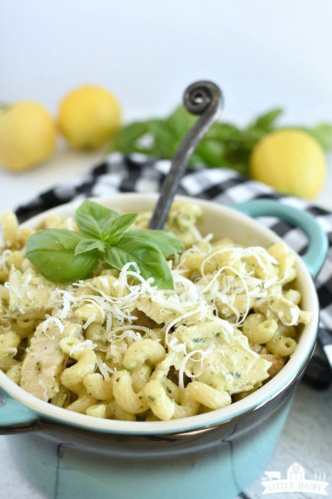 pesto pasta in a bowl with basil on top of it and a black spoon in it with lemons in the background on a black and white checkered napkin