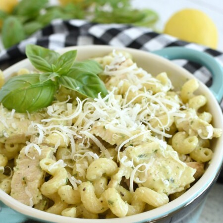 Pasta with grated parmesan cheese and grilled chicken on top of it in a blue dish, a black and white checkered napkin, lemons and basil in the background