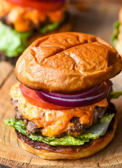 cheese burger with red onion, tomato slices, pimento cheese and lettuce
