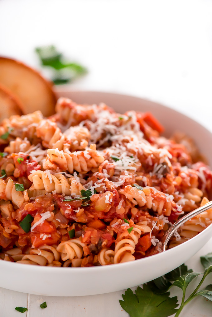 rotini pasta in a red sauce with grated parmesan cheese on top