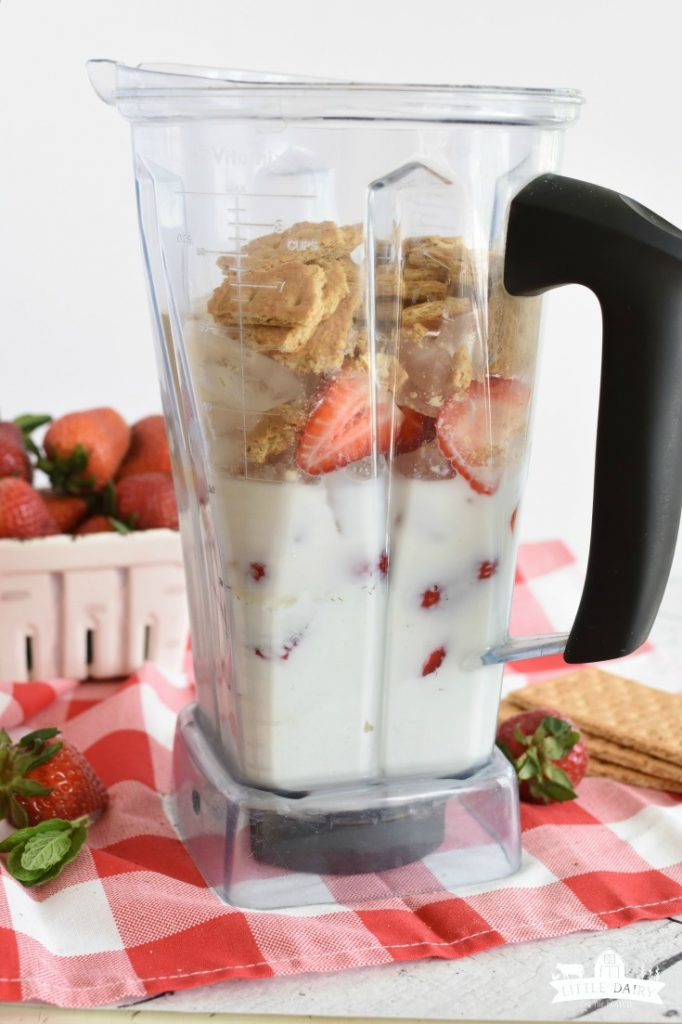 Blender with fresh strawberry cheesecake smoothies layer inside