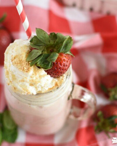 A top view of a mason jar with a strawberry smoothie with whipped cream on top