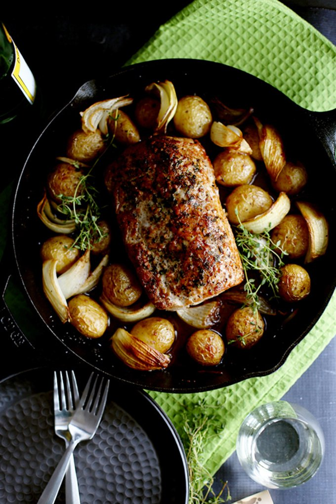 pork roast in a black pot with potatoes and thyme