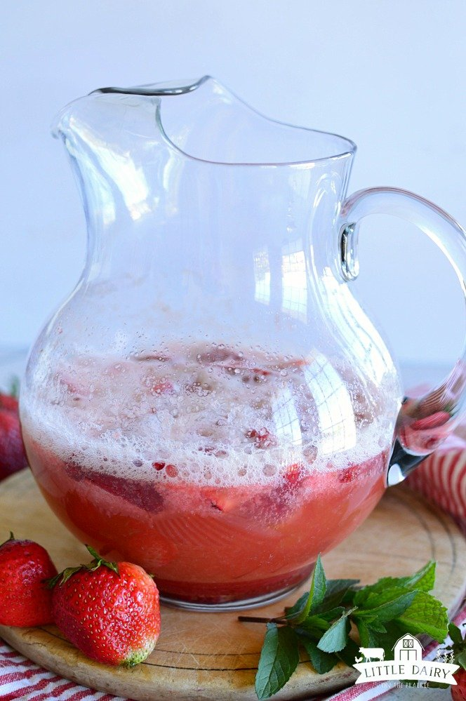 A glass pitcher a third full of a red drink with sliced strawberries on top and bubbles.