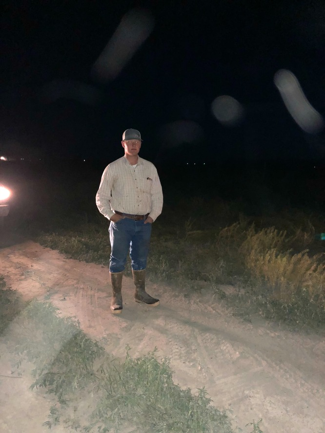 a teenage boy standing in the dark with rubber boots on