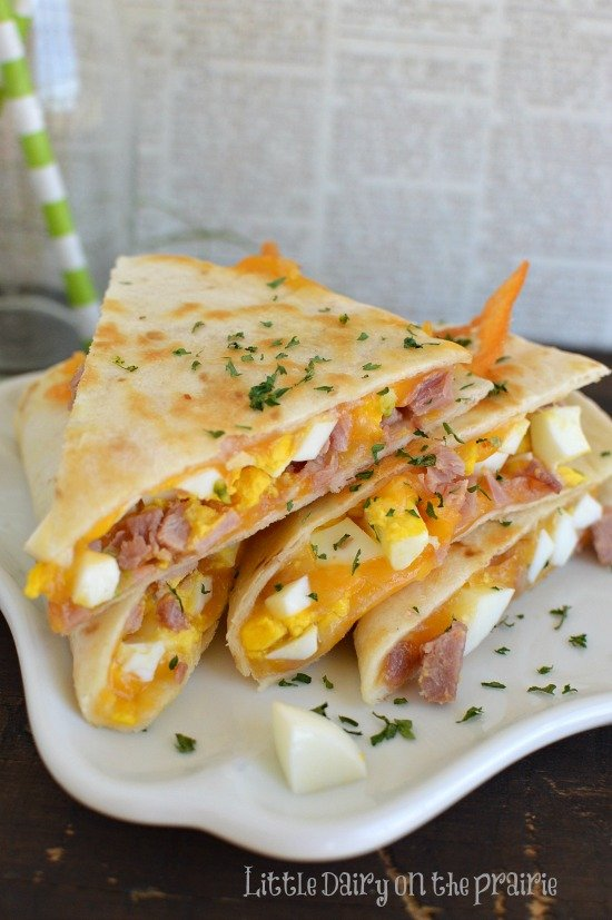 wedges of quesadilla with cheese, hard boiled eggs, and ham on a white plate with parsely sprinkled on top
