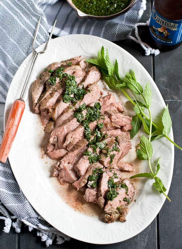 sliced leg of lamb on a white platter
