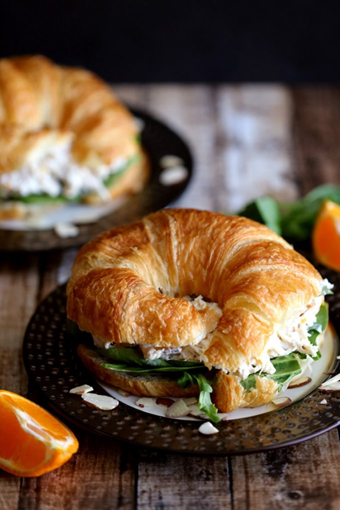 chicken salad on a croissant with green lettuce, on a black plate