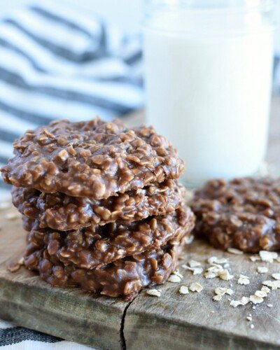 a stack of classic no bake cookies, a jar of milk, and one no bake cookie on a board with oat