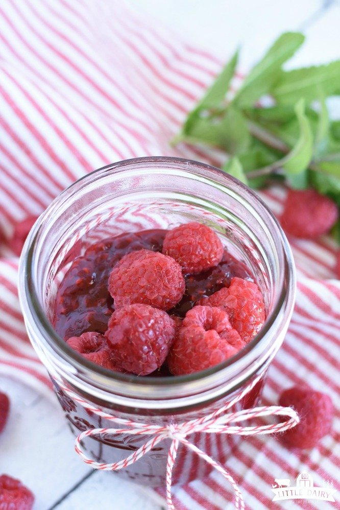 a canning jar with raspberry sauce and fresh raspberries on top, on a red and white striped napkin