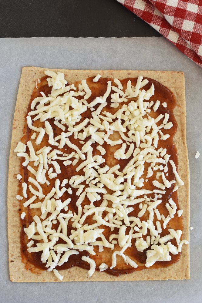 Flat bread pizza with red sauce and shredded cheese
