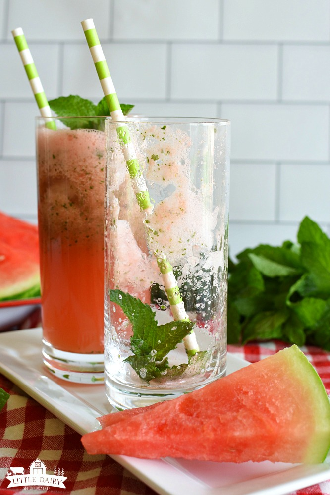 An empty glass with mint leaves and a straw, a full glass of watermelon lemonade behind it