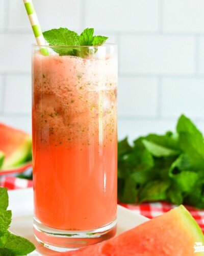 Red watermelon lemonade in a glass with mint leaves and a straw