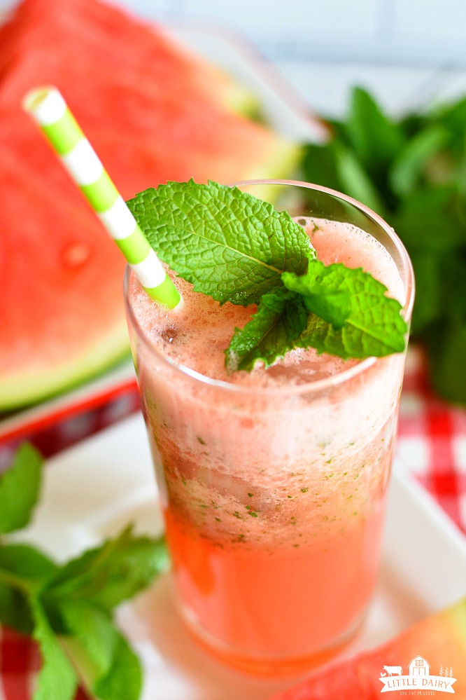 Top view of red watermelon lemonade with a mint sprig and a green and white straw