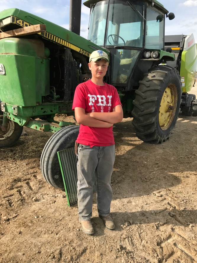 A boy in a red shirt standing in front of a john deere tractor