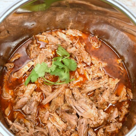 shredded pork roast in a pressure cooker in red liquid