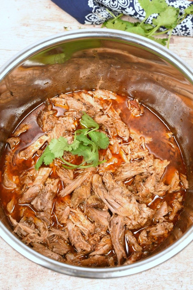 shredded pork roast in a pressure cooker in red liquid