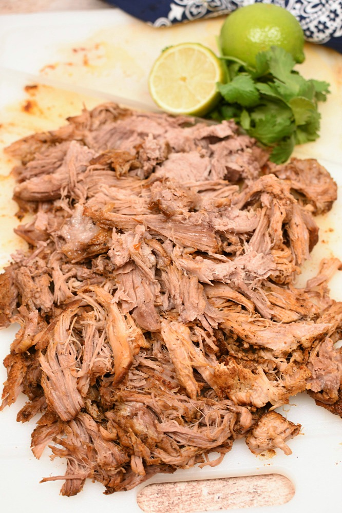 Shredded Mexican pork on a cutting board with a lime