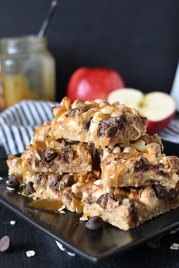 caramel apple crisp magic cookie bars stacked on a black plate