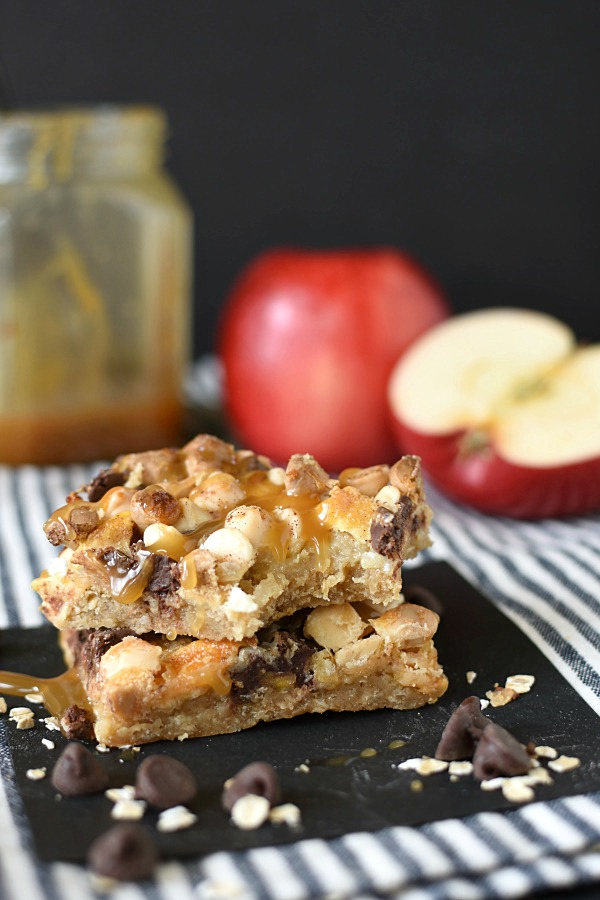 two caramel apple crisp magic cookie bars stacked on top of each other