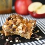 Caramel Apple Crisp Magic Cookie Bars have an oat crust, and are topped with apples, chocolate, coconut, and drizzled with sweetened condensed milk! pitchforkfoodie.com #cookies #barcookies #dessert #desserts #dessertbars #magiccookies #magicbars #apples #caramelapples #applecrisp #appledesserts #fivelayercookies #easyrecipe #recipe #sweettooth
