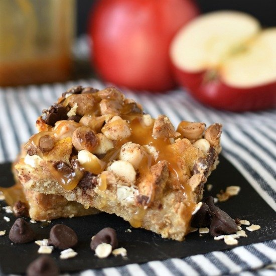 Caramel Apple Crisp Magic Cookie Bars have an oat crust, and are topped with apples, chocolate, coconut, and drizzled with sweetened condensed milk! www.littledairyontheprairie.com #cookies #barcookies #dessert #desserts #dessertbars #magiccookies #magicbars #apples #caramelapples #applecrisp #appledesserts #fivelayercookies #easyrecipe #recipe #sweettooth
