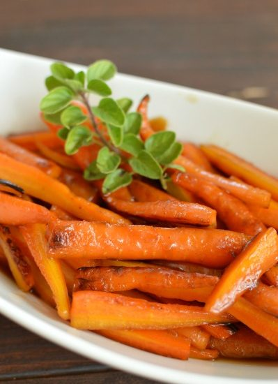 a white dish with glazed carrots and a sprig thyme