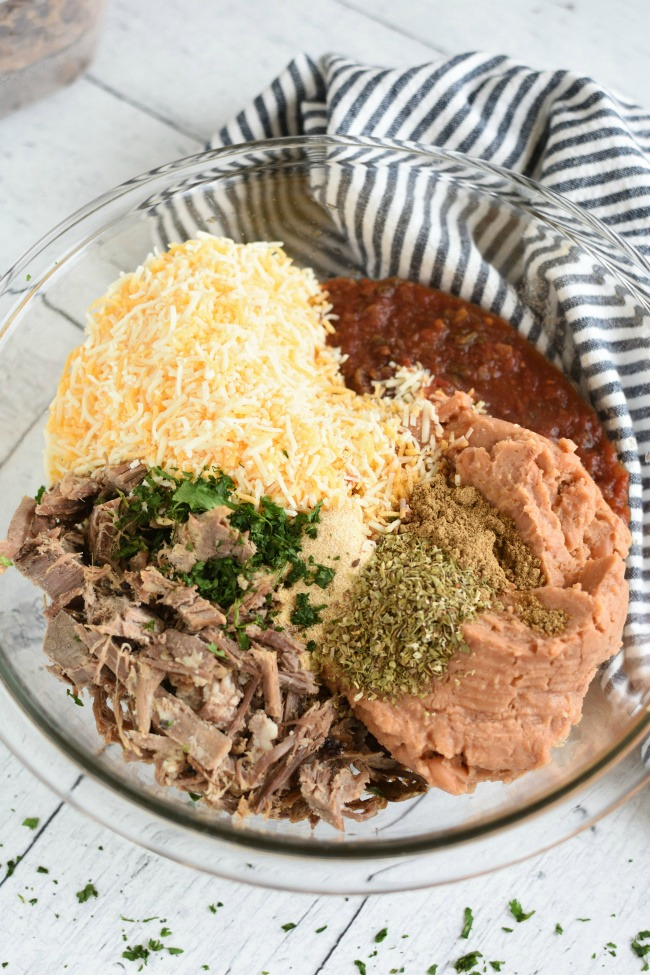 Shredded roast beef, burritos, shredded cheese, and spices in a bowl