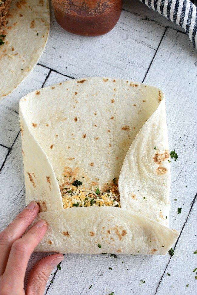 Flour tortilla with beef and bean filling being rolled up