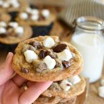 A hand holding a baked s'mores cookie