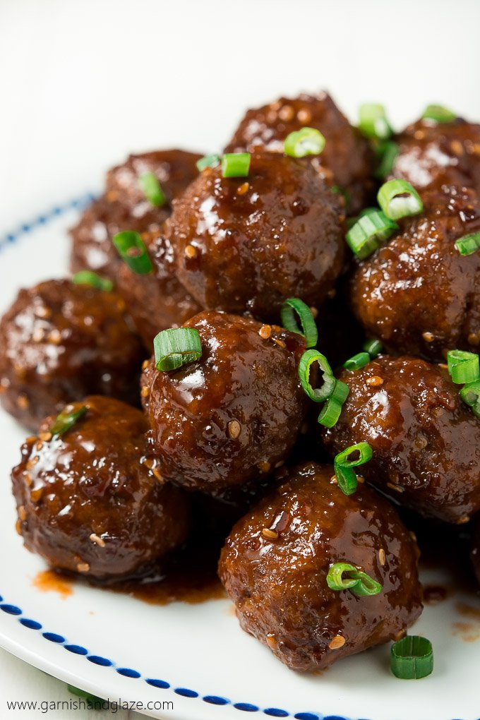 a white plate with meatballs coated in teriyaki sauce