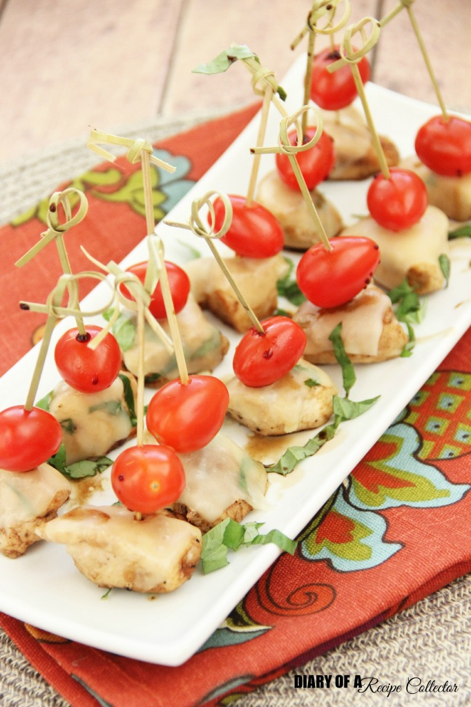 a white plate with chicken pieces topped with a cherry tomato and chopped basil, held together with a toothpick