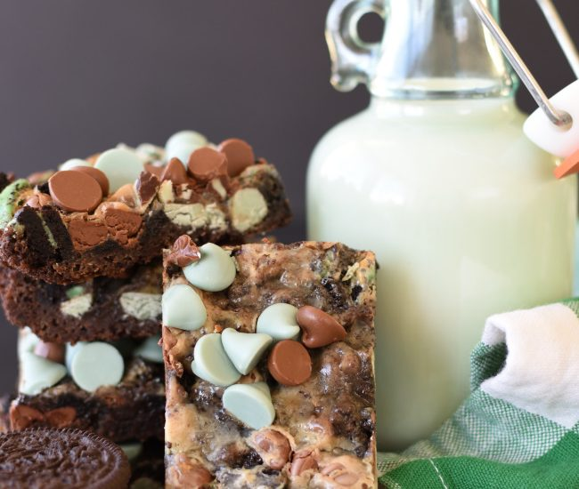 Mint Chocolate Magic Bar Cookies on a board with a container of milk and mint chocolate sandwich cookies
