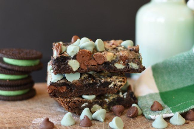 A stack of mint chocolate magic bars with a container of milk and a green and white napkin