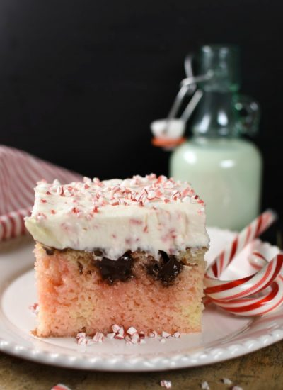Piece of white poke cake with pink marbeling, chocolate, and cheescake topping