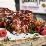 chicken drumsticks and raspberries on a wood board