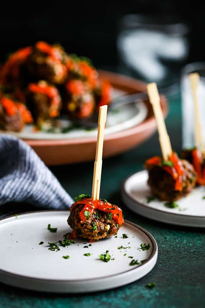 meatballs with a wooden skewer in them, topped with red chili paste and chopped parsley flakes
