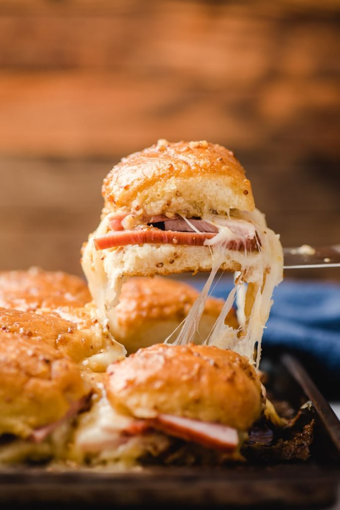 a gooey ham and cheese slider being lifted out of a baking dish with a spatula