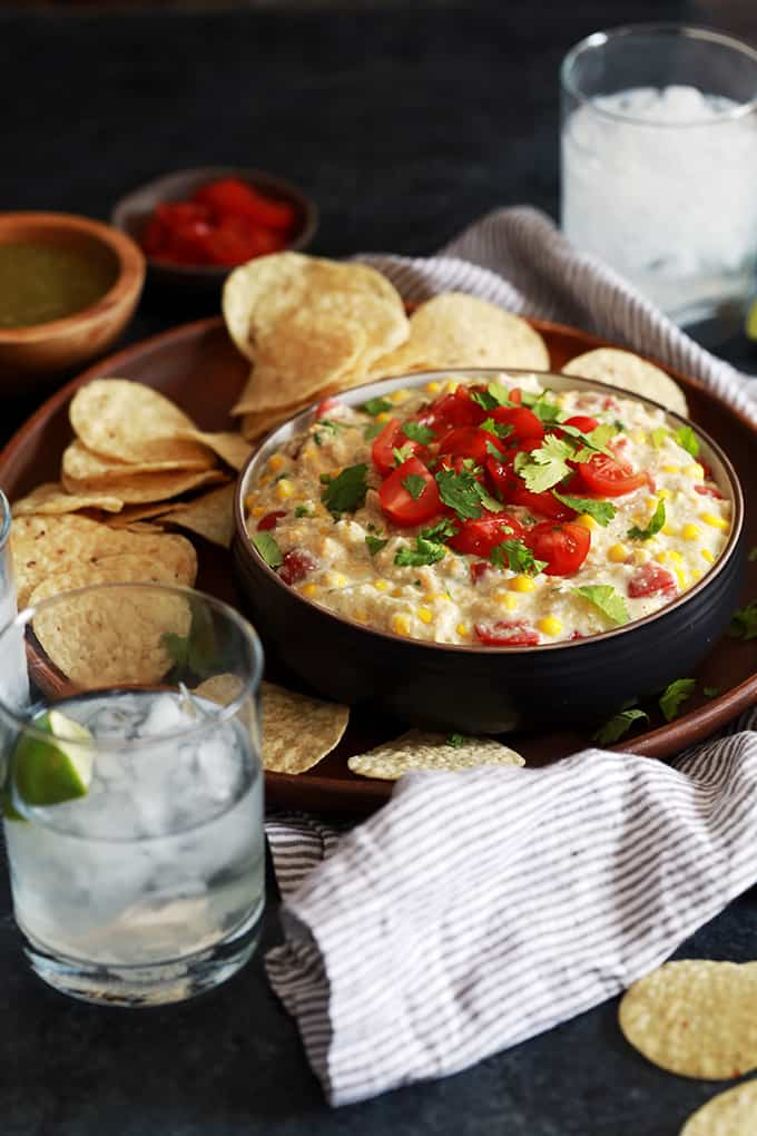 tortilla chips scattered around a bowl of corn dip topped with chopped tomatoes