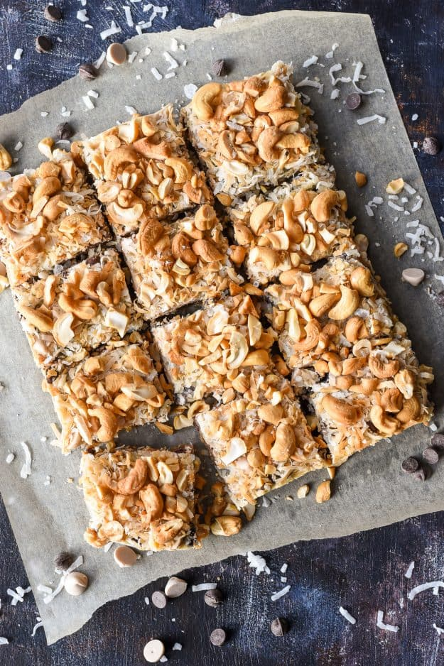 a batch of magic bar squares with coconut and cashews on a paper