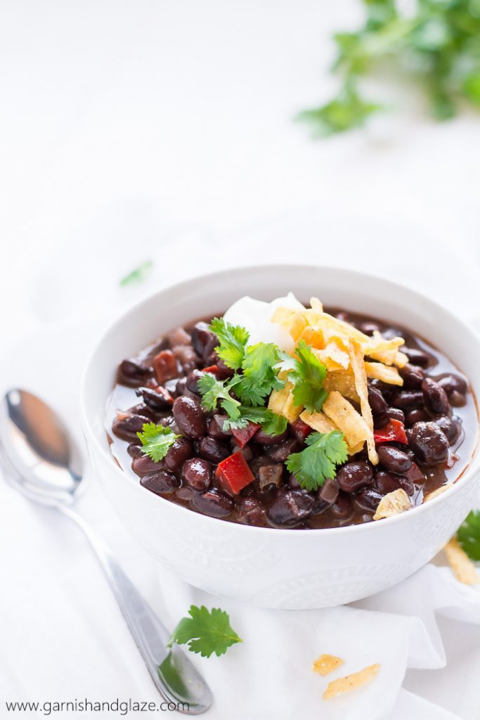 a white bowl with black bean soup topped with cilantro, tortilla chips, and sour cream