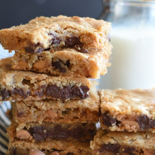 a stack of baked bar cookies with chocolate chips and butterscotch cookies