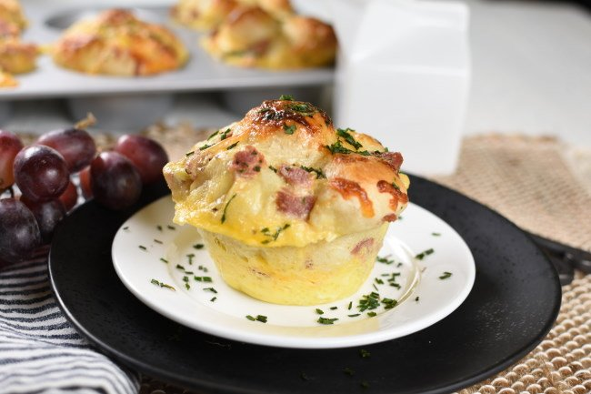 baked breakfast monkey bread with ham on a white plate with parsley sprinkled over the top