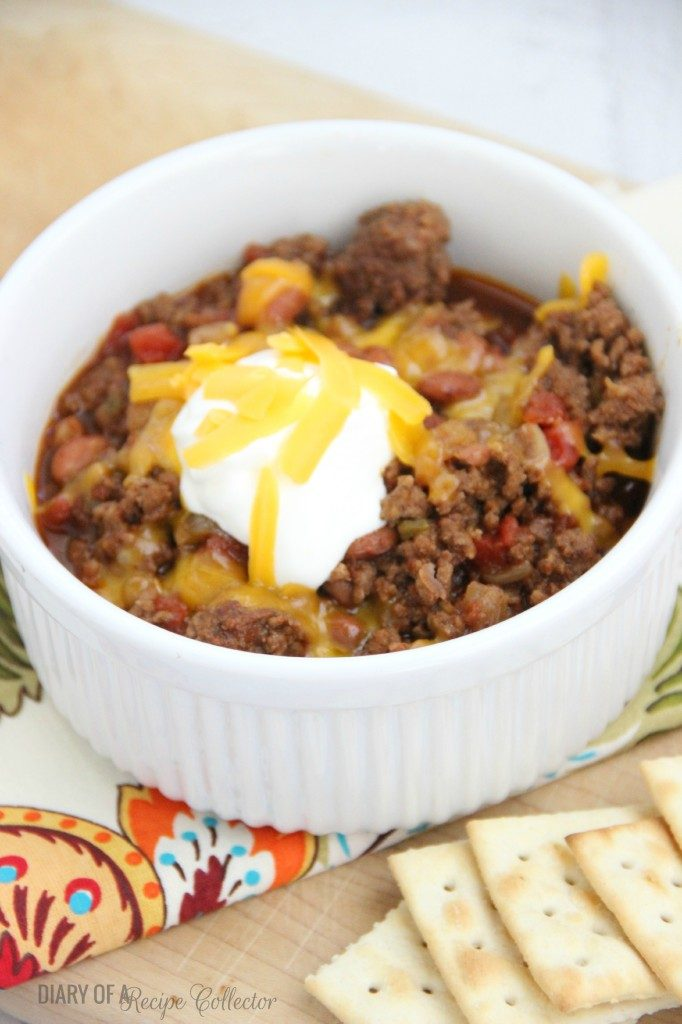A bowl of ground beef chili topped with sour cream and cheese